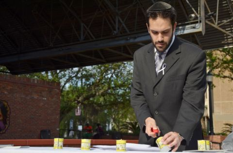 Rabbi Daniel Wolnerman, of UF Hillel, lights a candle at a memorial ceremony commemorating genocide victims on Bo Diddley Community Plaza on Sunday. April is Genocide Awareness Month. Photo courtesy Tony Sadiku, Alligator
