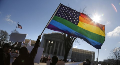 A gay activist waves a gay pride American flag outside the Supreme Court on March 26 | Reuters