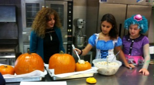 Students help fill the hollow pumpkins before baking