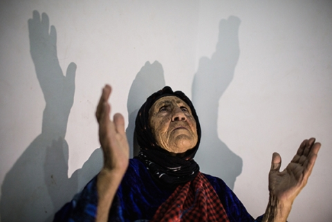 A displaced Iraqi Christian woman prays at the home where she is staying in Erbil. Photo courtesy of Mackenzie Knowles-Coursin for The United States Holocaust Memorial Museum.